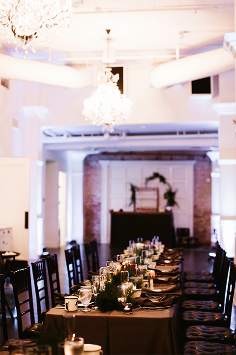 Orange county wedding at the estate on second dark brown wood table with gold place settings and white and green flower centerpiece decor with white glasses and candles and black chairs
