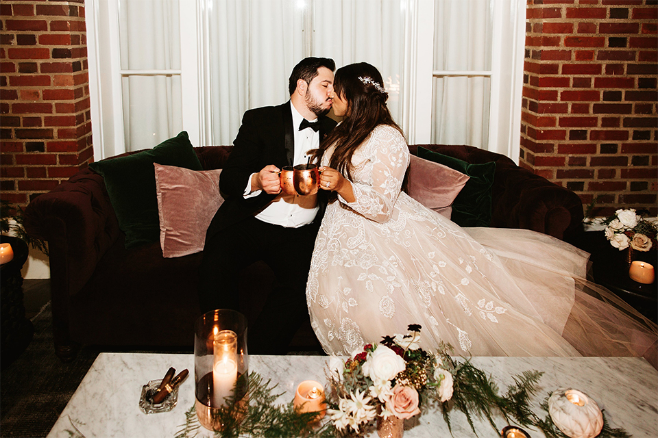 Orange county wedding at the estate on second bride lace ball gown with long sleeves and high neckline with crystal hair piece and groom black tuxedo with white dress shirt and black bow tie with white pocket square sitting on couch kissing