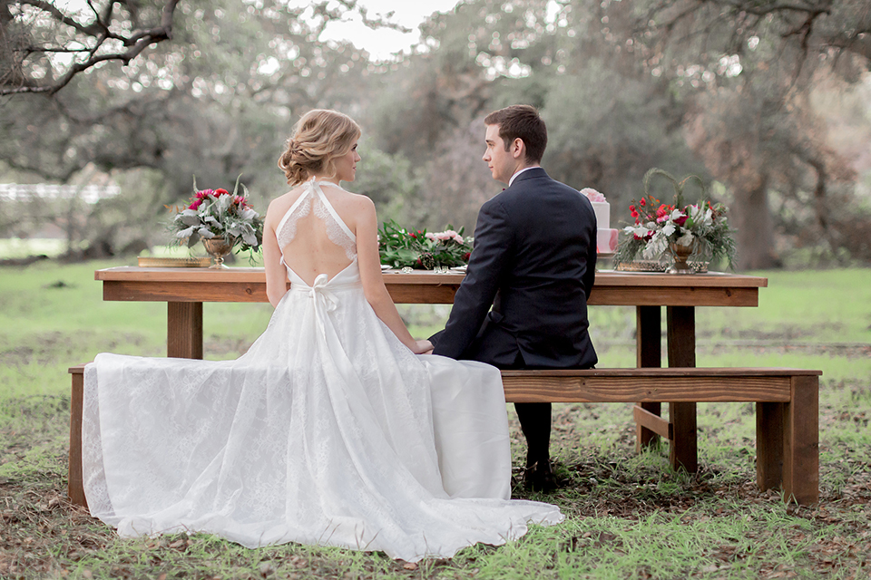 Valentine styled wedding shoot bride chiffon gown with halter straps and sweetheart neckline with groom navy blue suit with notch lapel with matching vest and white dress shirt with red bow tie and white floral boutonniere sitting at table