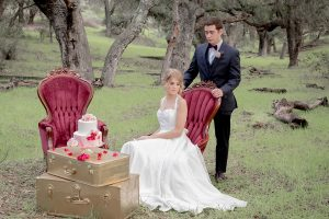 Valentine styled wedding shoot bride chiffon gown with halter straps and sweetheart neckline with groom navy blue suit with notch lapel with matching vest and white dress shirt with red bow tie and white floral boutonniere sitting in lounge furniture
