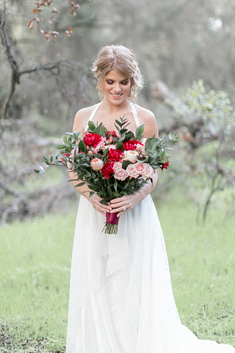 Valentine styled wedding shoot bride chiffon gown with halter straps and sweetheart neckline holding red and pink floral bridal bouquet