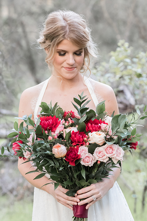 Valentine styled wedding shoot bride chiffon gown with halter straps and sweetheart neckline holding red and pink floral bridal bouquet with red flower crown