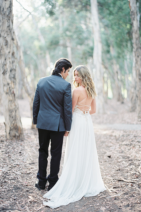 Into the woods outdoor romantic wedding shoot bride chiffon gown with thin spahetti straps and strap design on back with lace detail and sweetheart neckline with groom charcoal grey tuxedo coat with black lapels and black pants with white dress shirt and black bow tie holding hands