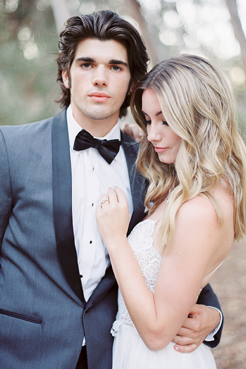 Into the woods outdoor romantic wedding shoot bride chiffon gown with thin spahetti straps and strap design on back with lace detail and sweetheart neckline with groom charcoal grey tuxedo coat with black lapels and black pants with white dress shirt and black bow tie hugging