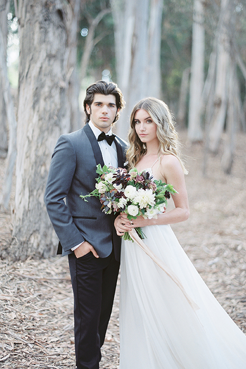 Into the woods outdoor romantic wedding shoot bride chiffon gown with thin spahetti straps and strap design on back with lace detail and sweetheart neckline with groom charcoal grey tuxedo coat with black lapels and black pants with white dress shirt and black bow tie bride holding white and purple floral bridal bouquet