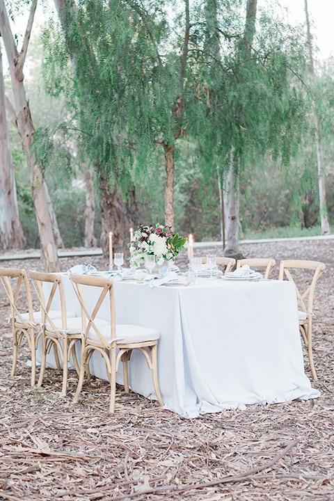 Into the woods outdoor romantic wedding shoot table set up white table linen with light brown wood chairs and white and purple flower centerpiece decor with white place settings and light blue linen napkin decor wedding photo idea