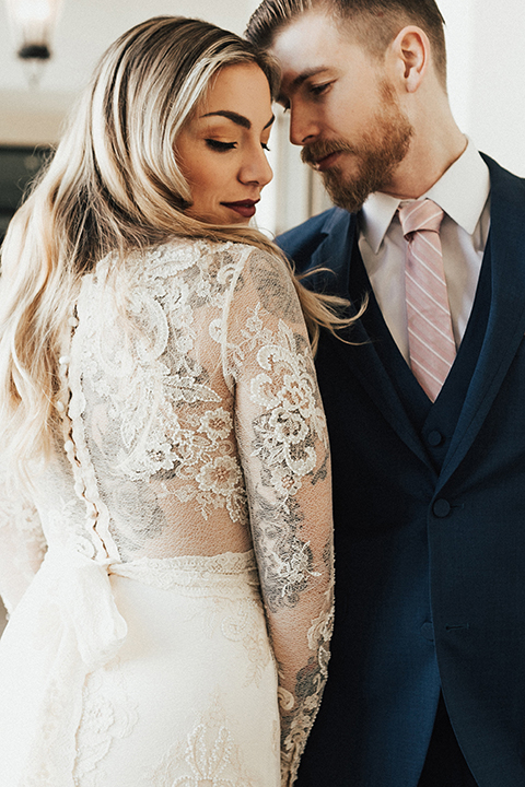 Dana point outdoor wedding shoot at monarch beach resort bride form fitting lace gown with long sleeves and high neckline with groom navy blue suit with matching vest and white dress shirt with long blush pink striped tie and matching pocket square hugging