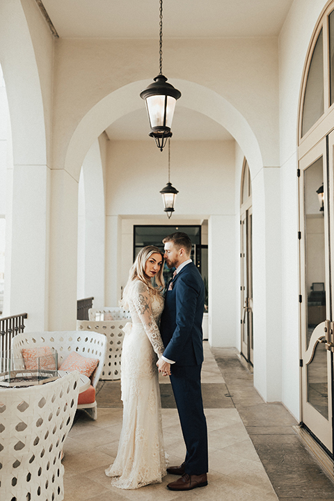 Dana point outdoor wedding shoot at monarch beach resort bride form fitting lace gown with long sleeves and high neckline with groom navy blue suit with matching vest and white dress shirt with long blush pink striped tie and matching pocket square holding hands and hugging