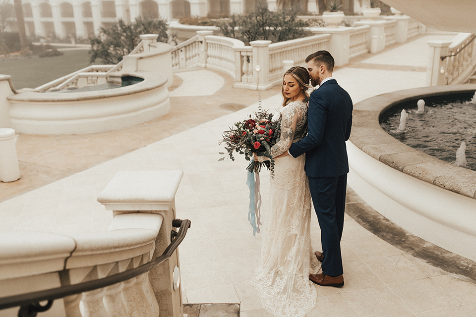 Dana point outdoor wedding shoot at monarch beach resort bride form fitting lace gown with long sleeves and high neckline with groom navy blue suit with matching vest and white dress shirt with long blush pink striped tie and matching pocket square hugging on steps