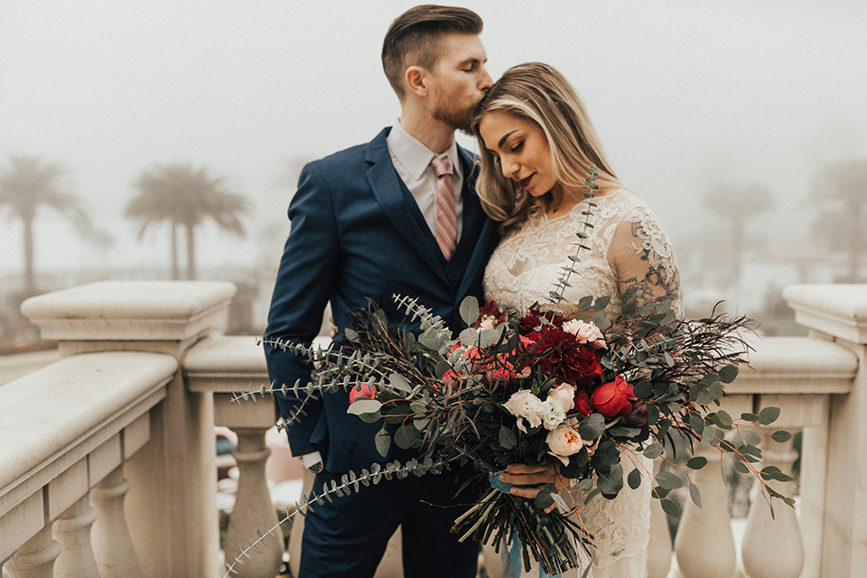 Dana point outdoor wedding shoot at monarch beach resort bride form fitting lace gown with long sleeves and high neckline with groom navy blue suit with matching vest and white dress shirt with long blush pink striped tie and matching pocket square bride holding red and green floral bridal bouquet
