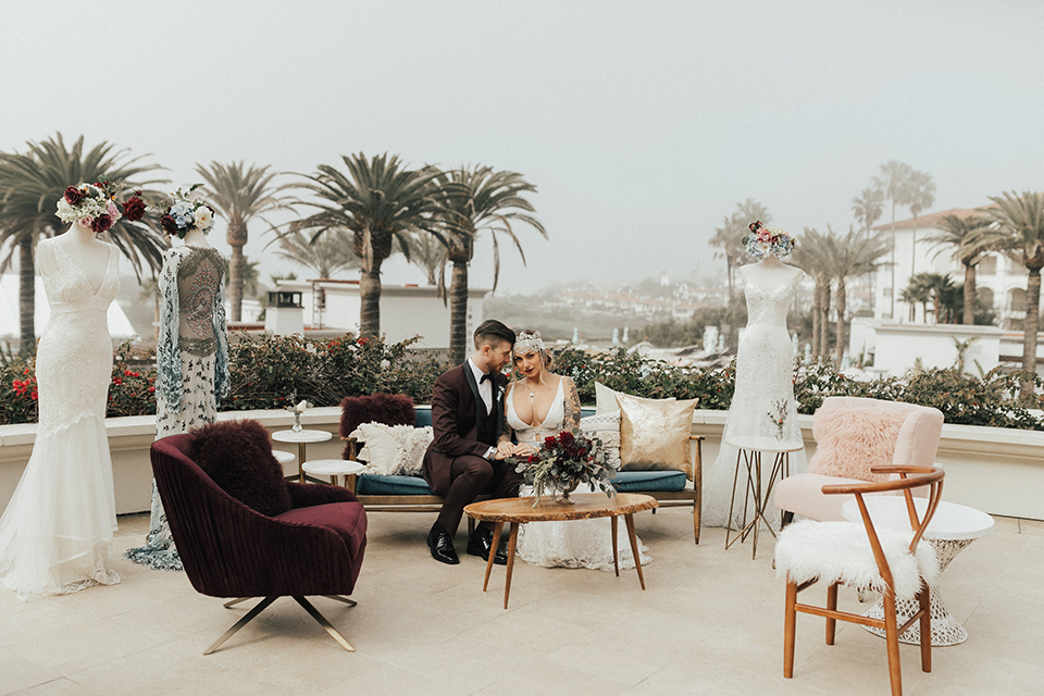 Dana point outdoor wedding shoot at monarch beach resort bride form fitting lace gown with thin straps and plunging neckline with groom burgundy tuxedo with matching vest and black bow tie with floral boutonniere sitting on couch