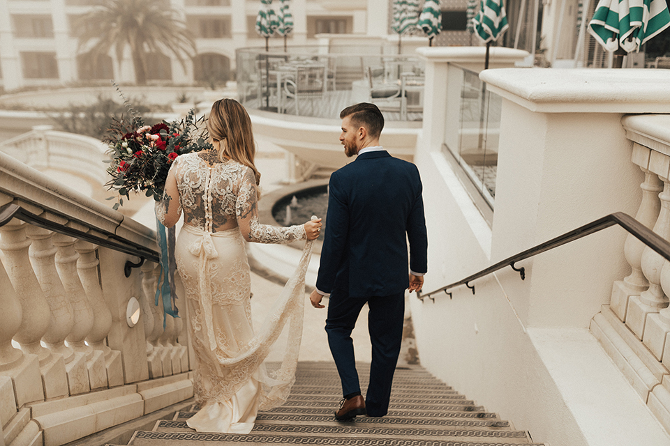 Dana point outdoor wedding shoot at monarch beach resort bride form fitting lace gown with long sleeves and high neckline with groom navy blue suit with matching vest and white dress shirt with long blush pink striped tie and matching pocket square walking down steps
