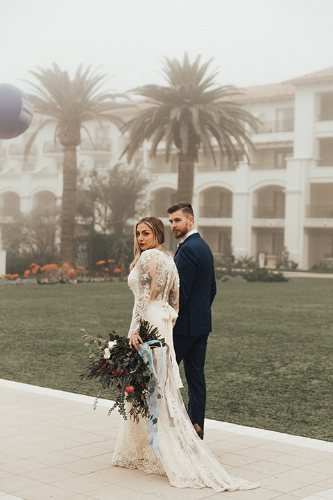 Dana point outdoor wedding shoot at monarch beach resort bride form fitting lace gown with long sleeves and high neckline with groom navy blue suit with matching vest and white dress shirt with long blush pink striped tie and matching pocket square walking and holding hands