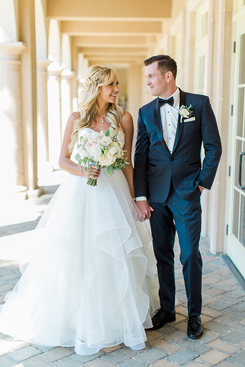 Laguna beach wedding bride ball gown with thin spaghetti straps and a sweetheart neckline with groom navy blue tuxedo with black shawl lapel and white dress shirt with black bow tie and white floral boutonniere holding hands and bride holding white and green floral bridal bouquet