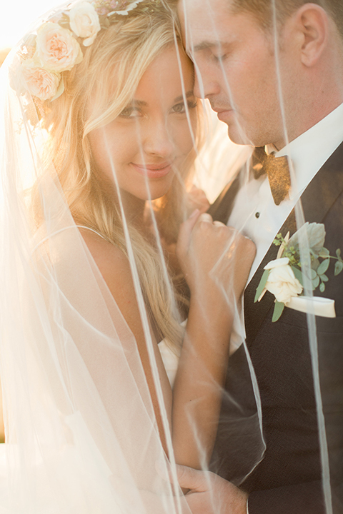 Laguna beach wedding bride ball gown with thin spaghetti straps and a sweetheart neckline with groom navy blue tuxedo with black shawl lapel and white dress shirt with black bow tie and white floral boutonniere hugging under veil