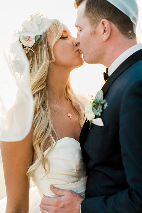Laguna beach wedding bride ball gown with thin spaghetti straps and a sweetheart neckline with groom navy blue tuxedo with black shawl lapel and white dress shirt with black bow tie and white floral boutonniere kissing