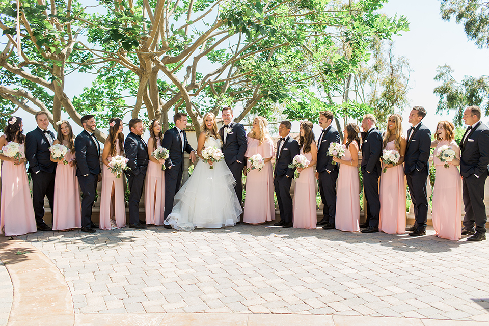 Laguna beach wedding bride ball gown with thin spaghetti straps and a sweetheart neckline with groom navy blue tuxedo with black shawl lapel and white dress shirt with black bow tie and white floral boutonniere with bridesmaids long blush pink dresses and groomsmen navy blue tuxedos with black bow ties