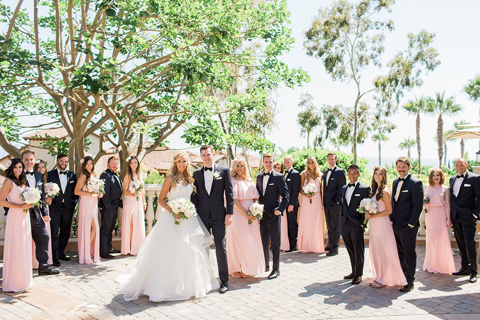Laguna beach wedding bride ball gown with thin spaghetti straps and a sweetheart neckline with groom navy blue tuxedo with black shawl lapel and white dress shirt with black bow tie and white floral boutonniere with bridesmaids long blush pink dresses with groomsmen navy blue tuxedos with black bow ties