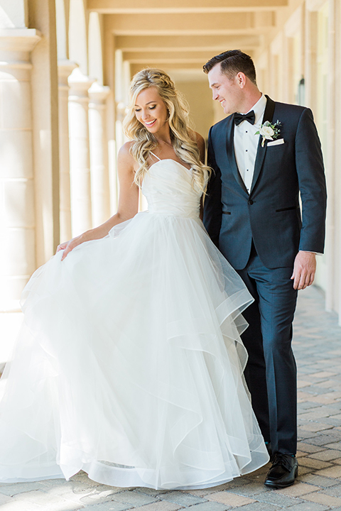 Laguna beach wedding bride ball gown with thin spaghetti straps and a sweetheart neckline with groom navy blue tuxedo with black shawl lapel and white dress shirt with black bow tie and white floral boutonniere hugging and bride holding dress