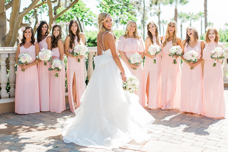 Laguna beach wedding bride ball gown with thin spaghetti straps and a sweetheart neckline holding white and green floral bridal bouquet with bridesmaids long blush pink dresses holding white floral bridal bouquets