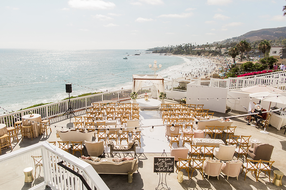 Laguna beach wedding ceremony set up with white aisle runner and gold chairs with gold altar with flower decor and white chairs in back with black and white sign for wedding ceremony wedding photo idea