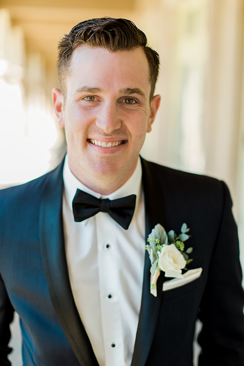 Laguna beach wedding groom navy blue tuxedo with a black shawl lapel and white dress shirt with black bow tie and white pocket square with white floral boutonniere
