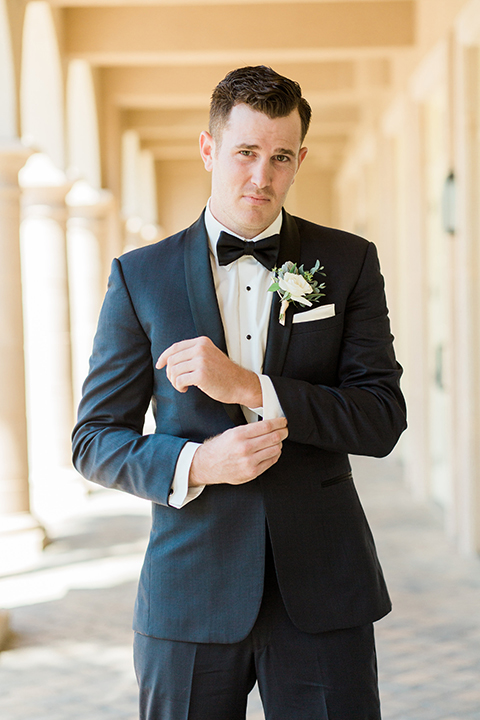 Laguna beach wedding groom navy blue tuxedo with a black shawl lapel and white dress shirt with black bow tie and white pocket square with white floral boutonniere holding jacket sleeve