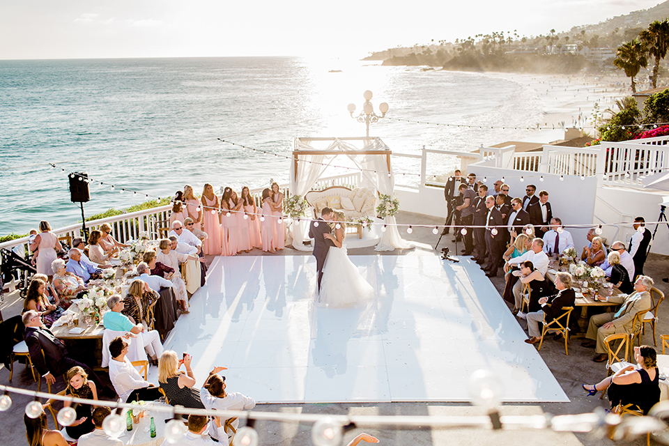 Laguna beach wedding bride ball gown with thin spaghetti straps and a sweetheart neckline with groom navy blue tuxedo with black shawl lapel and white dress shirt with black bow tie and white floral boutonniere first dance with ocean view and hanging lights