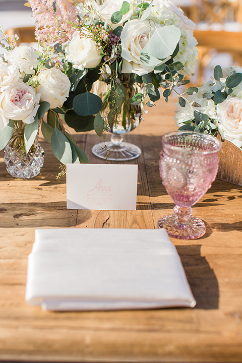 Laguna beach wedding table set up light brown wood table with light pink glasses and white and pink flower centerpiece decor with geometric shaped decor and white place settings with light brown chairs