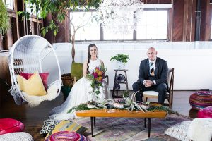 Santa barbara greenery wedding shoot at the narrative loft bride two piece gown with high neckline crop top and tulle skirt with pink and yellow floral bridal bouquet with groom grey suit with matching vest and white dress shirt with long striped tie and floral boutonniere sitting on chairs