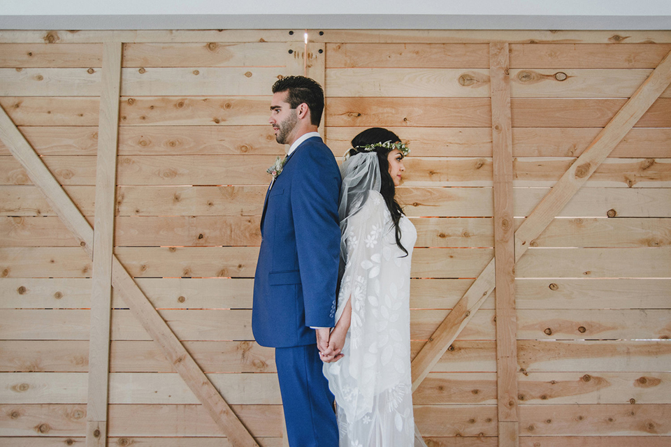 Orange county wedding at the colony house bride long sleeve lace gown with big sleeves and plunging neckline with sheer details with groom cobalt blue suit with matching vest and white dress shirt with long black skinny tie and white floral boutonniere holding hands