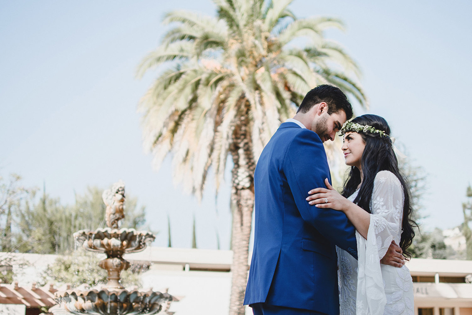 Orange county wedding at the colony house bride long sleeve lace gown with big sleeves and plunging neckline with sheer details with groom cobalt blue suit with matching vest and white dress shirt with long black skinny tie and white floral boutonniere hugging