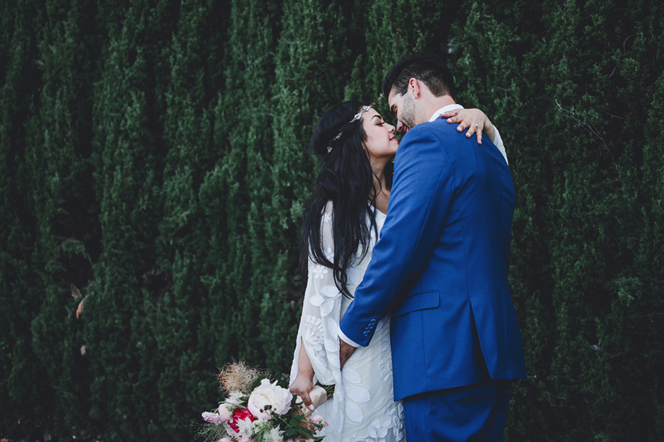 Orange county wedding at the colony house bride long sleeve lace gown with big sleeves and plunging neckline with sheer details with groom cobalt blue suit with matching vest and white dress shirt with long black skinny tie and white floral boutonniere hugging bride holding white and pink floral bridal bouquet