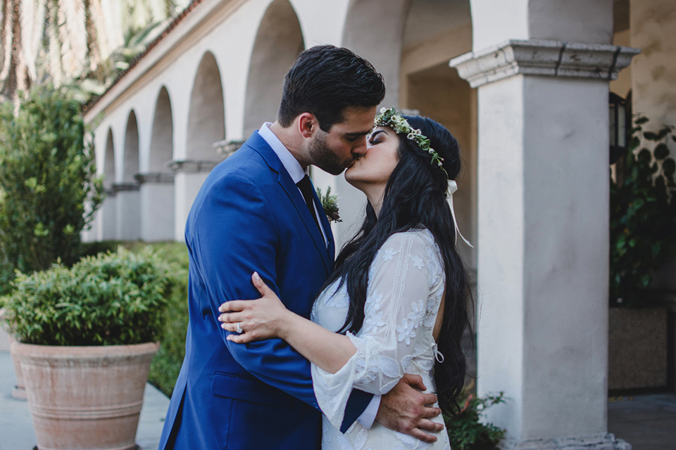 Orange county wedding at the colony house bride long sleeve lace gown with big sleeves and plunging neckline with sheer details with groom cobalt blue suit with matching vest and white dress shirt with long black skinny tie and white floral boutonniere kissing