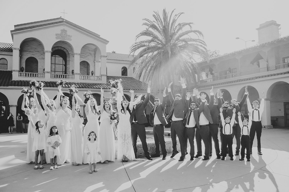 Orange county wedding at the colony house bride long sleeve lace gown with big sleeves and plunging neckline with sheer details with groom cobalt blue suit with matching vest and white dress shirt with long black skinny tie and white floral boutonniere with bridesmaids long blush pink dresses and groomsmen cobalt blue suits cheering black and white