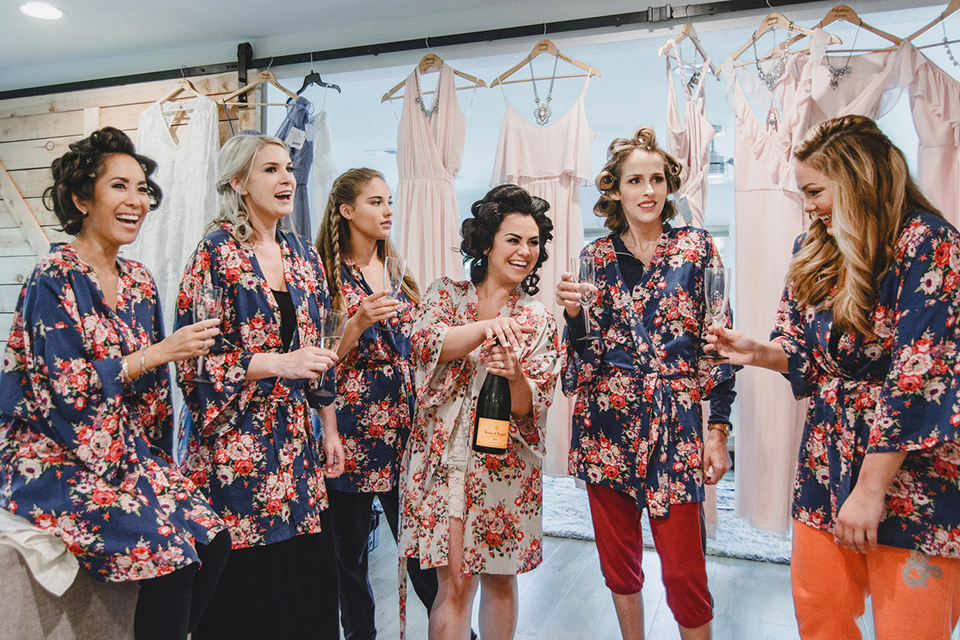 Orange county wedding at the colony house bride white and pink floral silk robe with hair in curlers getting ready with bridesmaids blue and pink floral robes with champagne