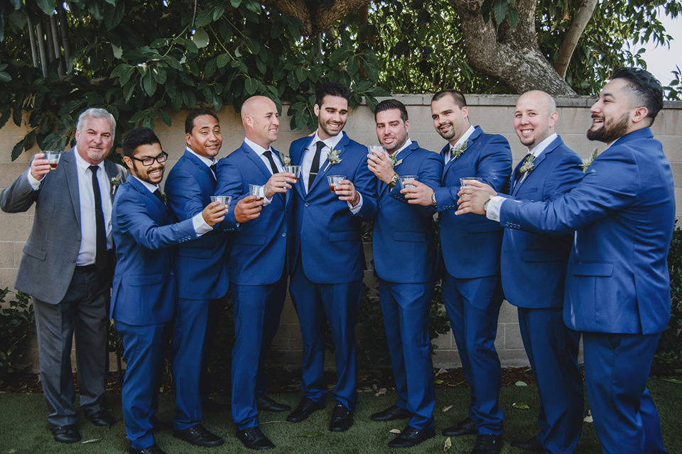 Orange county wedding at the colony house groom cobalt blue suit with matching vest and white dress shirt with long black skinny tie and white floral boutonniere with groomsmen holding drinks cobalt blue suits with matching vests and white dress shirts with long black skinny ties