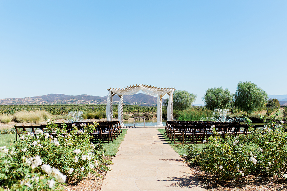 Temecula outdoor wedding at ponte winery ceremony set up with wooden altar with white chiffon and flower decor wedding photo idea for ceremony
