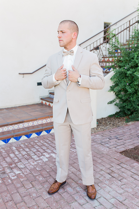 Temecula outdoor wedding at ponte winery groom tan suit with matching vest and white dress shirt with matching tan bow tie holding jacket