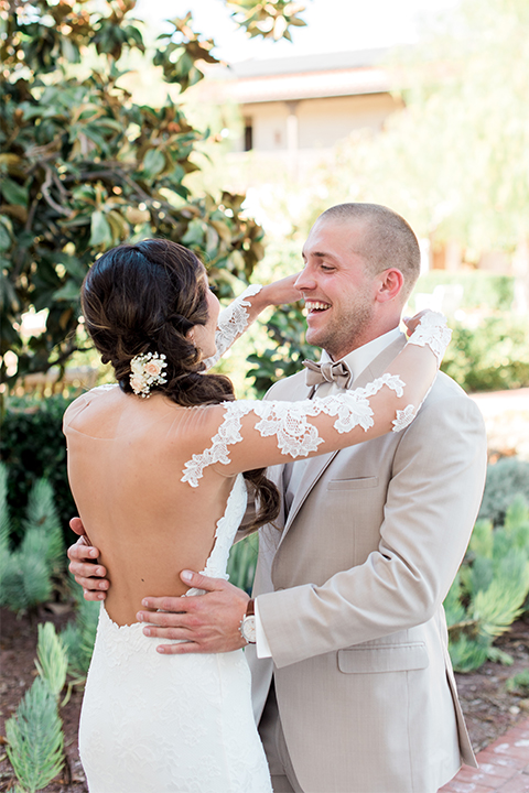 Temecula outdoor wedding at ponte winery bride form fitting lace gown with long sleeves and illusion open back design with sweetheart neckline and groom tan suit with matching vest and white dress shirt with matching tan bow tie and white floral boutonniere hugging first look