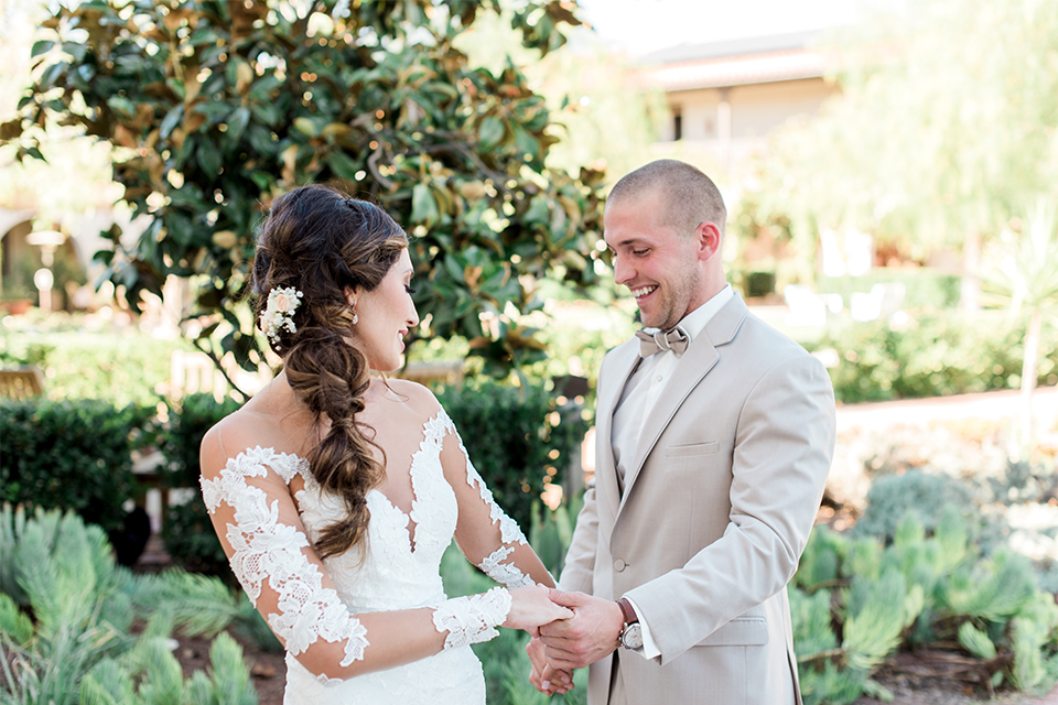 Temecula outdoor wedding at ponte winery bride form fitting lace gown with long sleeves and illusion open back design with sweetheart neckline and groom tan suit with matching vest and white dress shirt with matching tan bow tie and white floral boutonniere holding hands after first look
