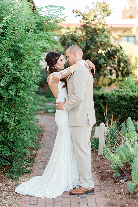 Temecula outdoor wedding at ponte winery bride form fitting lace gown with long sleeves and illusion open back design with sweetheart neckline and groom tan suit with matching vest and white dress shirt with matching tan bow tie and white floral boutonniere hugging