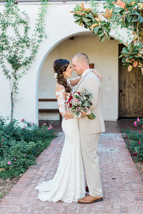 Temecula outdoor wedding at ponte winery bride form fitting lace gown with long sleeves and illusion open back design with sweetheart neckline and groom tan suit with matching vest and white dress shirt with matching tan bow tie and white floral boutonniere hugging bride holding white and red floral bridal bouquet