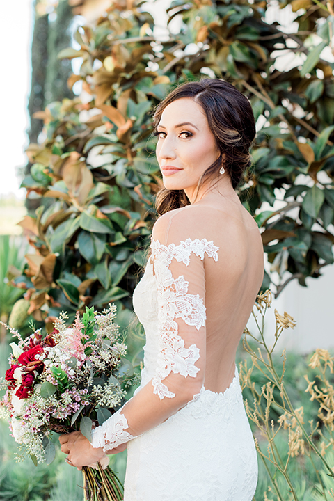 Temecula outdoor wedding at ponte winery bride form fitting lace gown with long sleeves and illusion open back design with sweetheart neckline holding white and red floral bridal bouquet