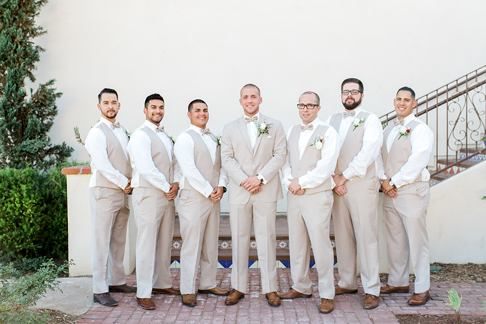 Temecula outdoor wedding at ponte winery groom tan suit with matching vest and white dress shirt with matching tan bow tie with white floral boutonniere with groomsmen tan suits with matching tan vests and tan bow ties