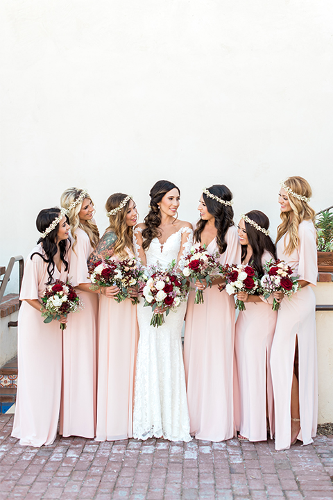 Temecula outdoor wedding at ponte winery bride form fitting lace gown with long sleeves and illusion open back design with sweetheart neckline holding white and red floral bridal bouquet with bridesmaids long blush pink dresses holding white and red floral bridal bouquets with flower crowns