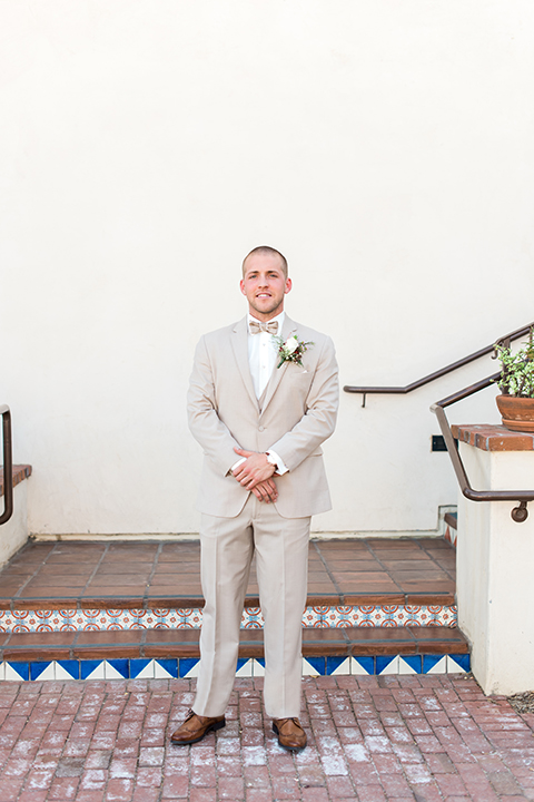 Temecula outdoor wedding at ponte winery groom tan suit with matching vest and white dress shirt with matching tan bow tie with white floral boutonniere