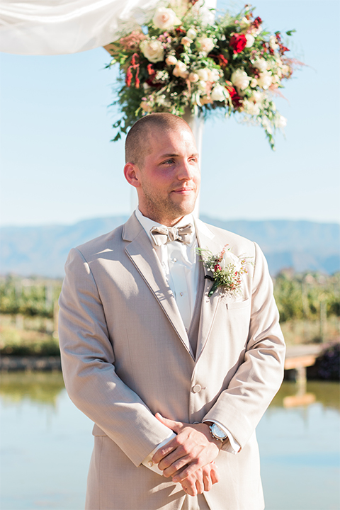 Temecula outdoor wedding at ponte winery groom tan suit with matching vest and white dress shirt with matching tan bow tie with white floral boutonniere watching bride walking down the aisle wedding photo idea for groom