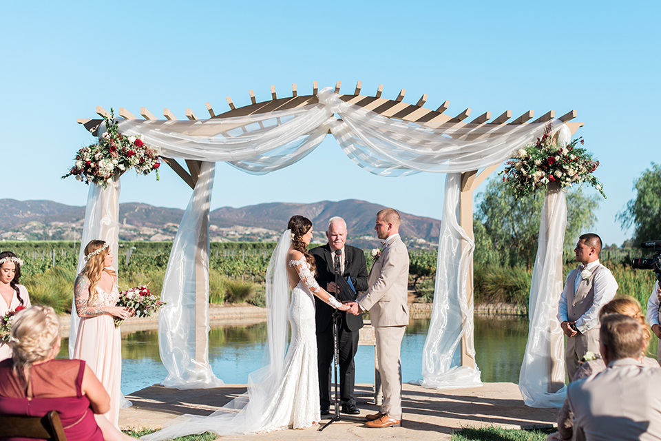 Temecula outdoor wedding at ponte winery bride form fitting lace gown with long sleeves and illusion open back design with sweetheart neckline and groom tan suit with matching vest and white dress shirt with matching tan bow tie and white floral boutonniere holding hands during ceremony