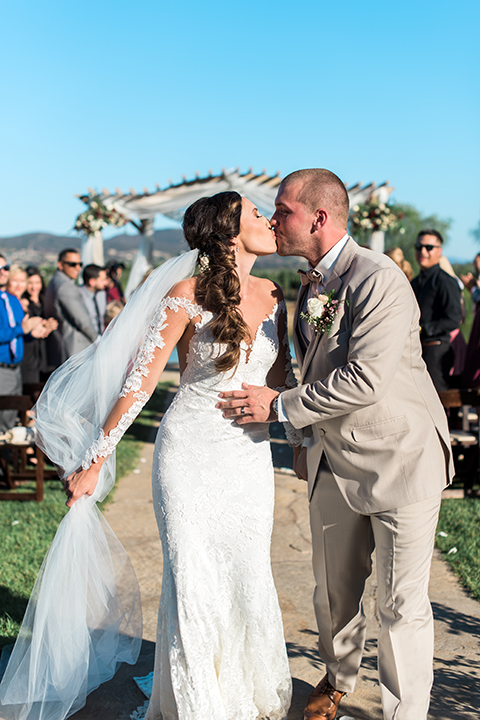 Temecula outdoor wedding at ponte winery bride form fitting lace gown with long sleeves and illusion open back design with sweetheart neckline and groom tan suit with matching vest and white dress shirt with matching tan bow tie and white floral boutonniere kissing in aisle after ceremony